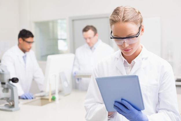 Wissenschaftler, der tablette während kollegen hinten arbeiten verwendet