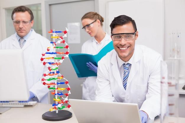 Wissenschaftler, der zusammen mit laptop und computer arbeitet