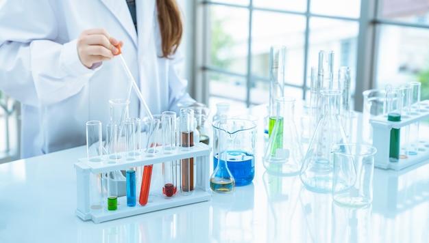 Wissenschaftler des jungen mädchens, der experimente chemisch im glasrohr im laborraum macht