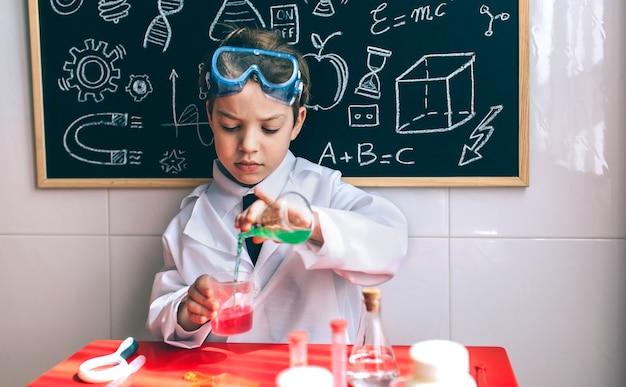 Wissenschaftler des kleinen jungen, der chemische grüne flüssigkeit aus der flasche gegen die tafel mit zeichnungen gießt