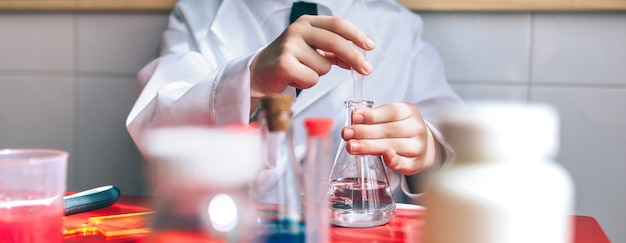 Wissenschaftler des kleinen jungen, der flüssigkeit aus der flasche gegen die tafel mit zeichnungen extrahiert. selektiver fokus auf kolben.