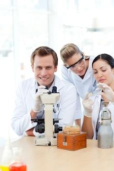 Wissenschaftler, die ein dia unter einem mikroskop betrachten