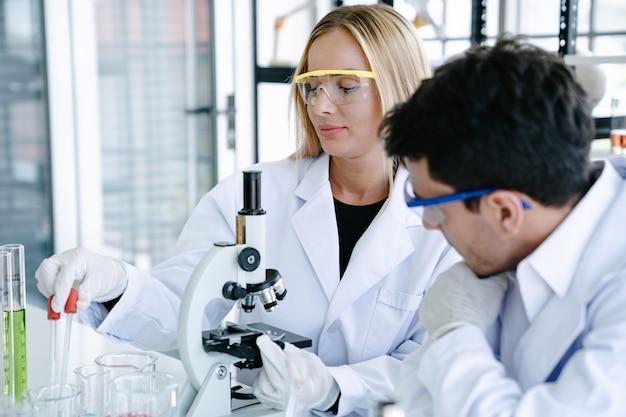 Wissenschaftler, die medizinische flüssigkeit mit mikroskop beim handeln der gesundheitswesenforschung im labor überprüfen