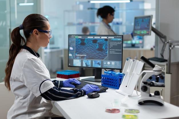 Wissenschaftler forscher chemiker frau tippt mikrobiologische testkompetenz