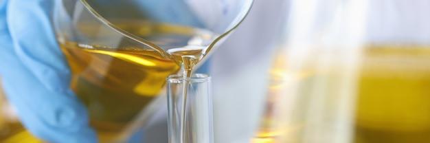 Wissenschaftler gießt klare goldene flüssigkeit in glaskolben-motorölproduktionstechnologiekonzept