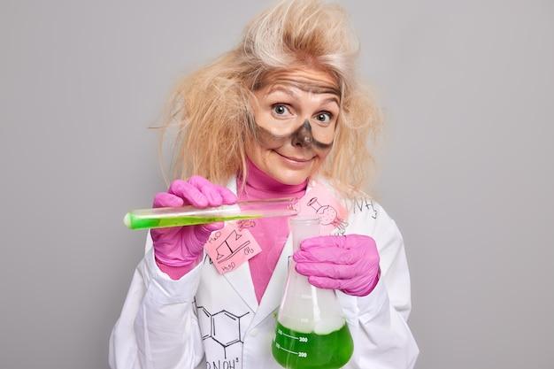 Wissenschaftler hält becher und reagenzglas in wissenschaftlicher forschung mischt zutaten führt chemische laborexperimente durch trägt medizinische mantelgummihandschuhe isoliert auf grau