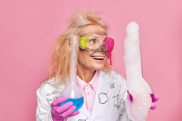 Wissenschaftler hält glaskolben lässt das experiment die reaktion mit blasen betrachten, nachdem die reagenzien gemischt wurden, freut sich über das ergebnis der lösungsdestillation