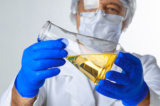 Wissenschaftler hände halten etwas flüssigkeit in einem glas im labor zur analyse
