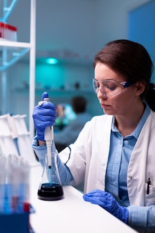 Wissenschaftler im gesundheitswesen, der während der impfstoffentwicklung eine labortropfer-mikropipette verwendet