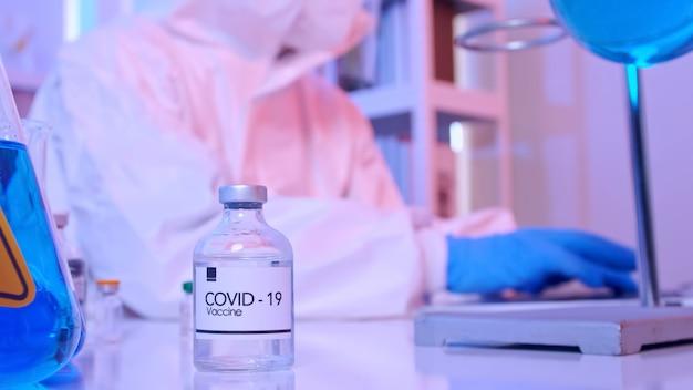Wissenschaftler im psa-anzug forschen in einem labor am covid 19-impfstoff.