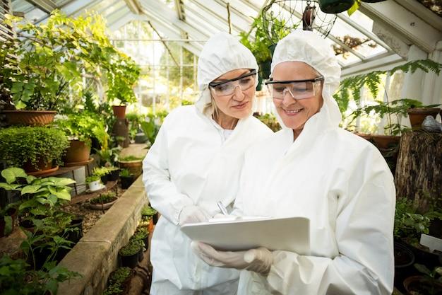 Wissenschaftler im sauberen anzug betrachten die zwischenablage, während sie pflanzen untersuchen