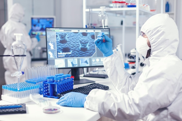 Wissenschaftler im schutzanzug, der eine probe von infiziertem blut mit coronavirus im reagenzglas hält
