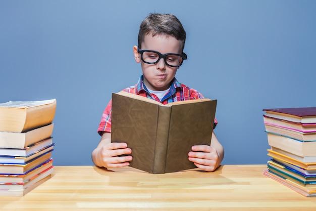 Wissenschaftler kleines kind in gläsern, die ein buch in der schulbibliothek lesen. bildungskonzept