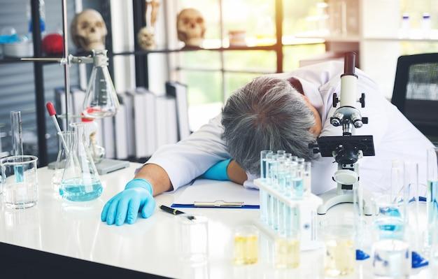 Wissenschaftler mann, der verzweifelt verzweifelt ernsthaft gestresst ist, probleme mit schulden hat, er schläft auf dem tisch und er ist müde von wissenschaftlichen experimenten.