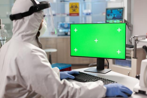 Wissenschaftler-mann mit schutzanzug, der am computer mit grünem modell tippt. team von mikrobiologen, die impfstoffforschung betreiben und auf gerät mit chroma-key schreiben, isolierte anzeige.