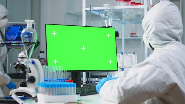 Wissenschaftler-mann mit schutzanzug, der auf dem computer mit grünem modell in einem modern ausgestatteten labor tippt. team von mikrobiologen, die impfstoffforschung betreiben und auf gerät mit chroma-key schreiben, isolierte anzeige.
