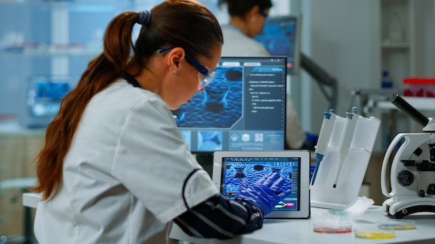 Wissenschaftler mit digitaler tablette, die im modernen medizinischen forschungslabor arbeitet und dna-informationen analysiert. medizin, biotechnologische forschung im fortgeschrittenen pharmalabor, untersuchung der virusevolution