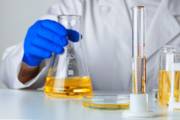 Wissenschaftler oder arzt in blauen handschuhen gießen etwas gelbe flüssigkeit in einen kolben