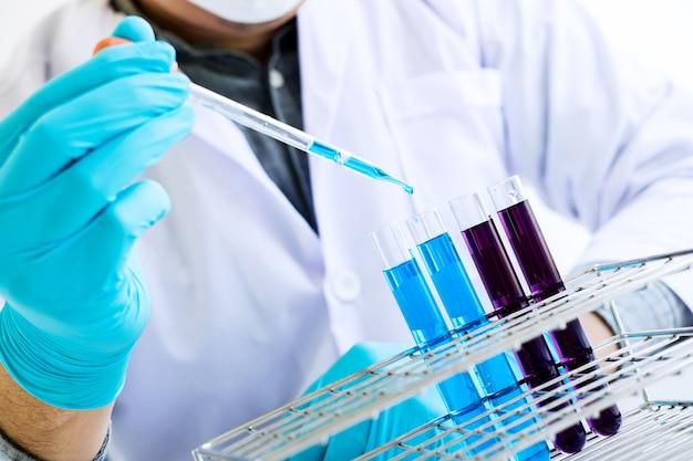 Wissenschaftler oder medizinisch im labormantel, der reagenzglas mit reagens mit tropfen der farbflüssigkeit hält