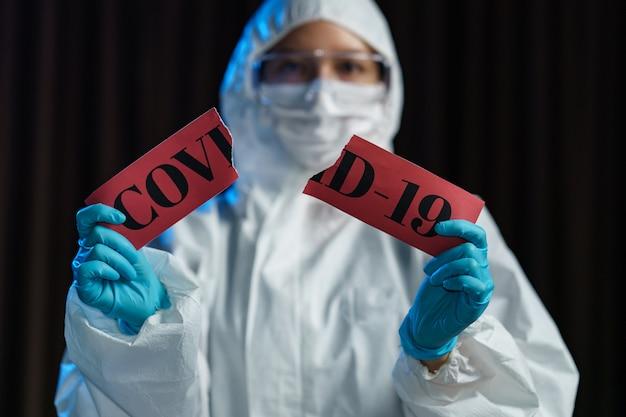 Wissenschaftler trägt medizinische maske mit schutzbrille im schutzanzug, handrissetikettenpapier mit dem text vorsicht covid-19.