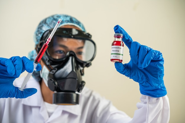 Wissenschaftler tragen masken und handschuhe halten eine spritze mit einem impfstoff, um covid-19 zu verhindern