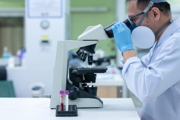 Wissenschaftler untersuchen die keime, die covid-19, die hauptursache für krankheiten, verursachen und sich weltweit verbreiten. (fokus auf röhre)