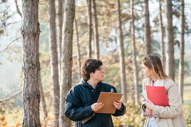 Wissenschaftler untersuchen pflanzenarten und untersuchen bäume im wald.