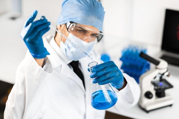 Wissenschaftler untersucht die flüssigkeit in einem medizinischen kolben