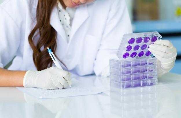 Wissenschaftlerhand hält testplatte von dengue-viren im labor