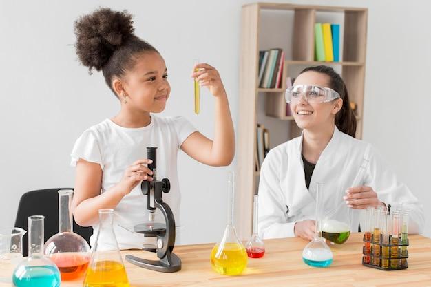 Wissenschaftlerin beobachtet mädchen, das mit chemie experimentiert