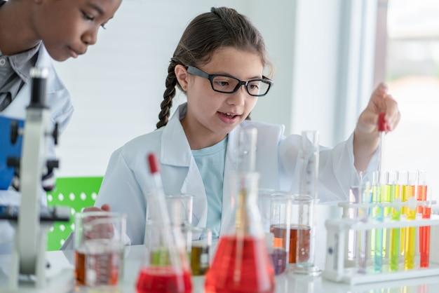 Wissenschaftlerin des kleinen mädchens, die chemische experimente in der glasröhre im laborraum macht