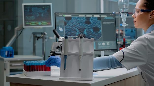 Wissenschaftlerin, die im labor mit chemischer technologie sitzt