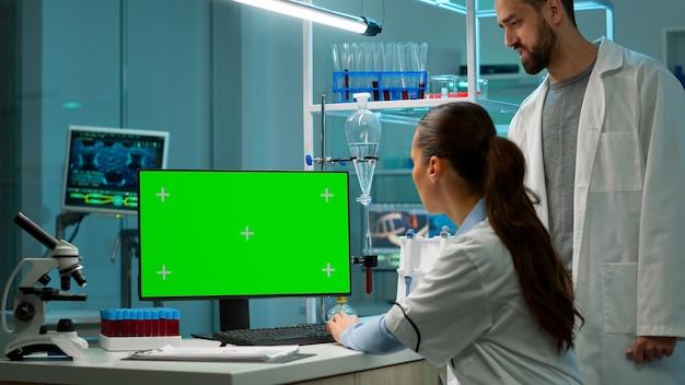 Wissenschaftlerin, die im modernen labor am computer mit grünem mock-up-bildschirm arbeitet. wissenschaftlerdoktor, der verschiedene regale mit bechern, chemikalien und verschiedenen technischen geräten verwendet, ist sichtbar.