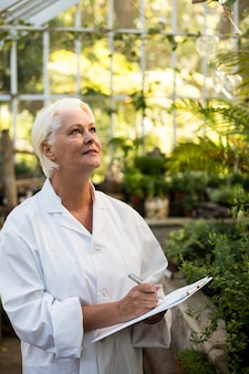 Wissenschaftlerin, die in zwischenablage schreibt, während pflanzen untersucht