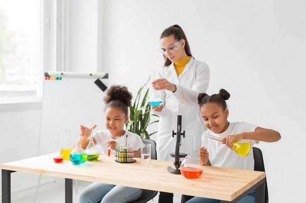 Wissenschaftlerin, die junge mädchen wissenschaftliche experimente unterrichtet