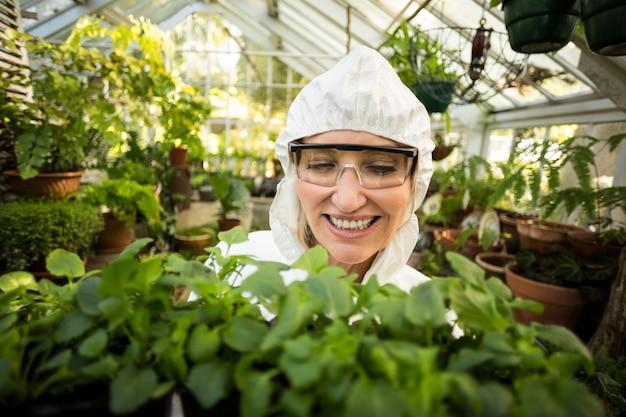 Wissenschaftlerin, die lächelt, während sie pflanzen hält