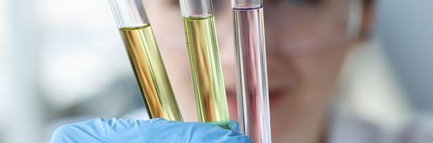 Wissenschaftlerin, die reagenzgläser mit bunten flüssigkeiten in ihren händen hält, nahaufnahmelabor