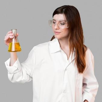 Wissenschaftlerin, die reagenzglas beim tragen der schutzbrille hält