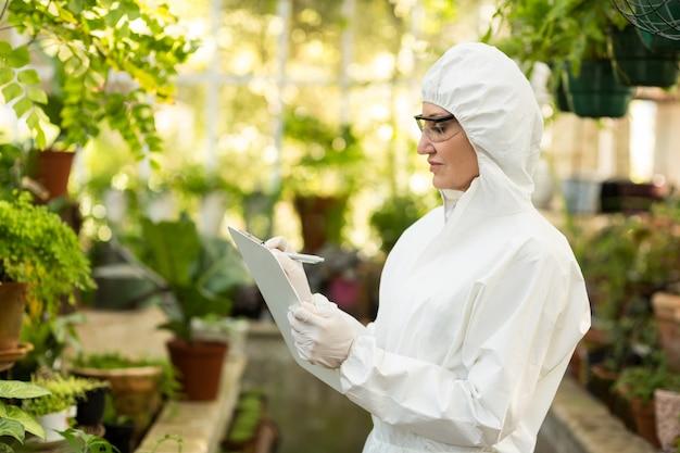 Wissenschaftlerin, die sauberen anzug trägt, der in zwischenablage schreibt