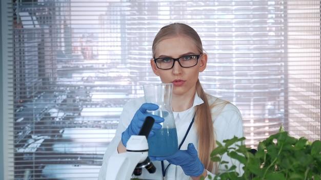 Wissenschaftlerin, die über den inhalt des erlenmeyerkolbens und das leitende experiment berichtet