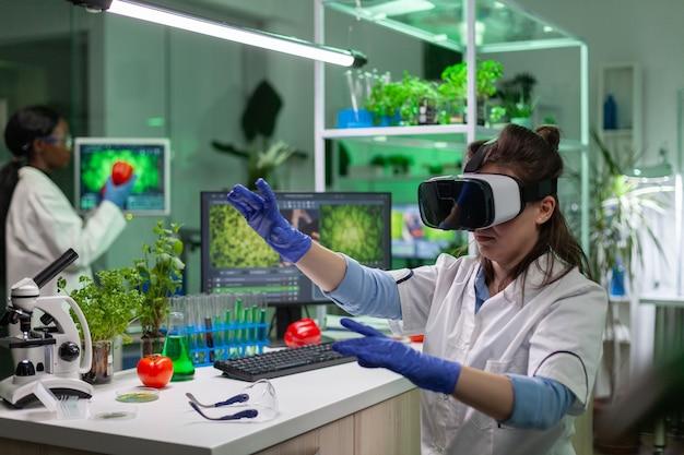 Wissenschaftlerin forscherin mit virtual-reality-headset entwickelt neue biotechnologie für biologische experimente. medizinisches team, das im mikrobiologielabor arbeitet, das dna-test analysiert.