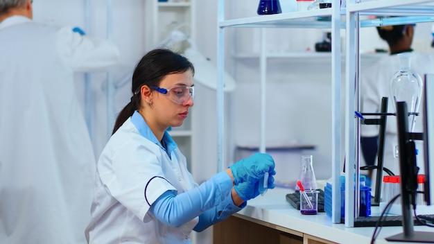 Wissenschaftlerin füllt flüssiges reagenzglas mit pipette im modern ausgestatteten labor. multiethnische medizin, die die entwicklung von impfstoffen mit high-tech-forschungsdiagnosen gegen das covid19-virus untersucht