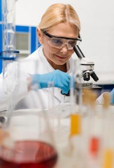 Wissenschaftlerin im labor mit mikroskop