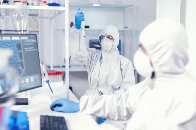 Wissenschaftlerin im overall mit mikropipette im labor für die coronavirus-forschung. team von mikrobiologen im forschungslabor, das während der globalen pandemie mit covid19 experimente durchführt.