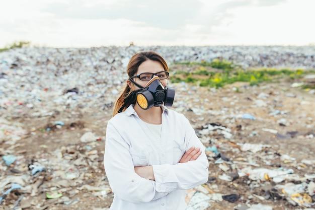 Wissenschaftlerin in einer atemschutzmaske auf einer deponie bewertet den grad der umweltverschmutzung