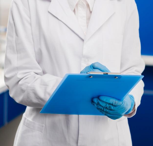 Wissenschaftlerin mit chirurgischen handschuhen, die etwas auf notizblock schreiben