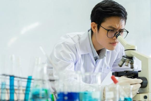 Wissenschaftlermann, der auf mikroskop schaut, um über chemikalie am laborraum nach forschung zu analysieren und sich zu entwickeln