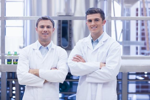 Wissenschaftlerteam, das an der kamera mit den armen gekreuzt lächelt