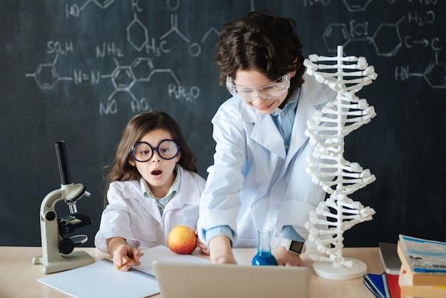 Wissenschaftliche sitzung junger kollegen. erstaunlich erfinderisch begeisterte schüler, die im labor stehen und die wissenschaft erforschen, während sie an dem projekt arbeiten und geräte verwenden