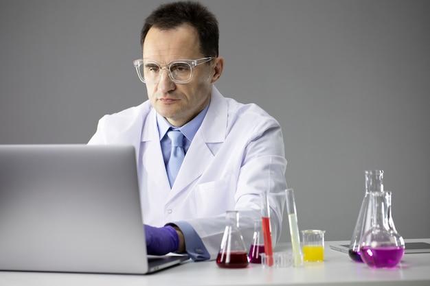 Wissenschaftlicher chemiker, der im labor mit reagenzgläsern und laptop-wissenschaftsausrüstung arbeitet